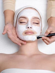 Cosmetician apllying healthy mask on face of young woman